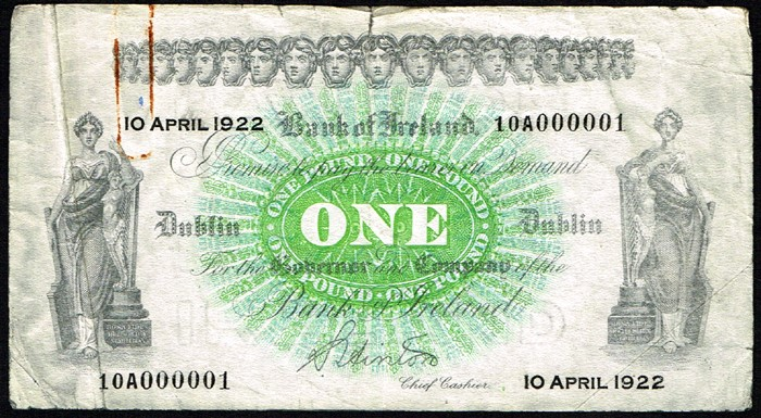1922 Bank of Ireland One Pound, 10 April 1922, serial number 10A000001. Signed S. Hinton. Tear at top centre, rustmarks from paper clip, about very fine